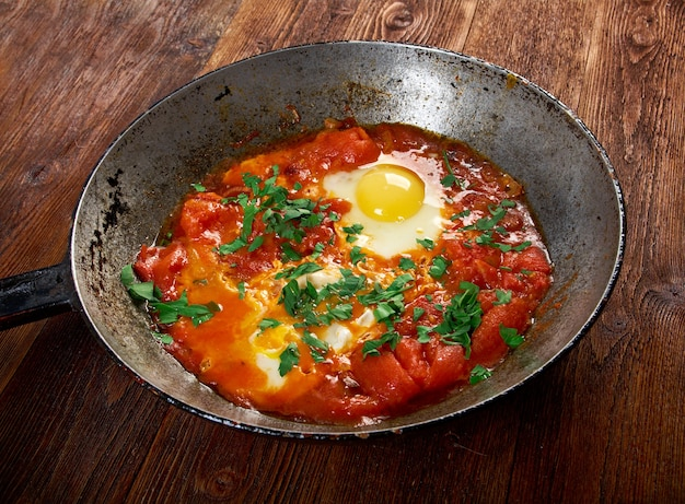シャクシューカ-トマト、唐辛子、玉ねぎのソースでポーチした卵の料理、しばしばクミンでスパイスを効かせます。伝統的にモロッコ料理、チュニジア料理、リビア料理、アルジェリア料理、エジプト料理