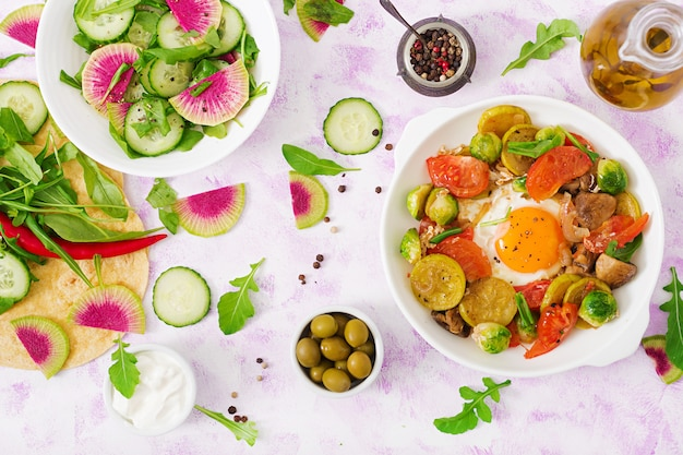 Shakshuka and fresh salad cucumber, watermelon radish and arugula
