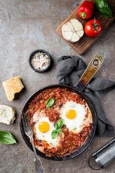 Шакшука, яичница в томатном соусе на железной сковороде. типичная израильская еда. вид сверху.