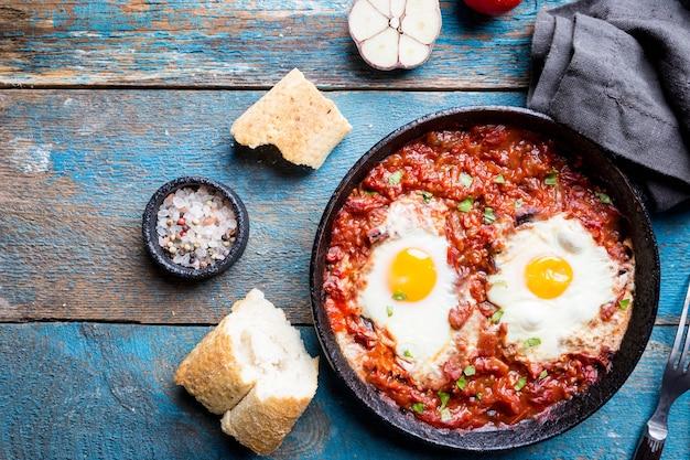 Шакшука, яичница в томатном соусе на железной сковороде