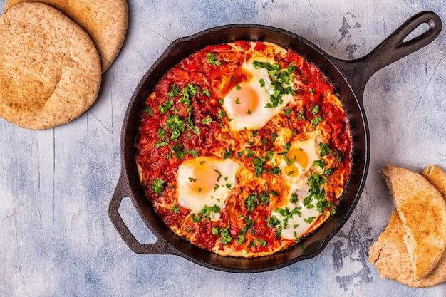 프라이팬에 넣은 shakshuka. 매운 토마토 후추 소스에 데친 계란.