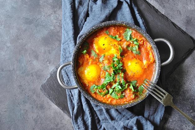 Шакшука в сковороде на серой деревенской поверхности. средние восточные традиционные блюда. яичница с овощами. пространство для текста. вид сверху.