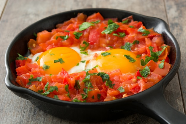 Shakshuka in iron frying pan on wooden table typical food in israel.