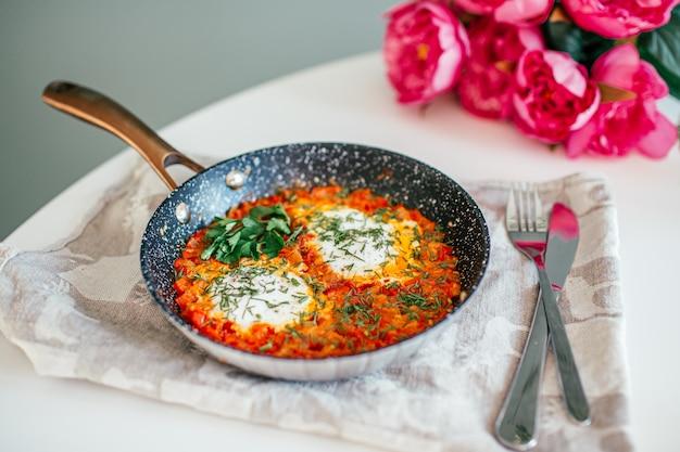 Шакшука с яйцами, болгарским перцем, помидорами и петрушкой в чугунной сковороде на белом столе с розовыми цветами на пространстве