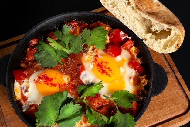 Shakshuka with pita bread in a pan on wooden desk on black background