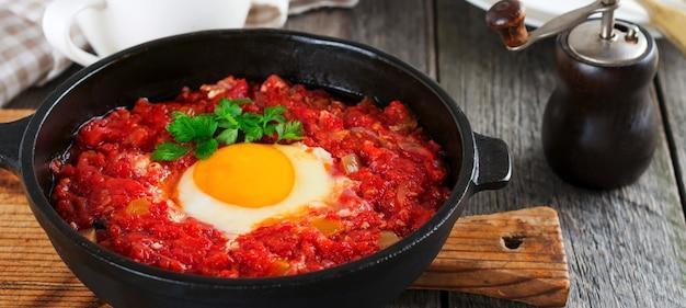 Шакшука с томатным соусом и жареным яйцом в чугунной сковороде на завтрак на старом деревянном фоне. деревенский стиль, выборочный фокус.