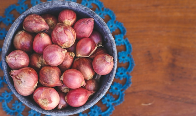 Shallot in a pot on wooden background with copy space