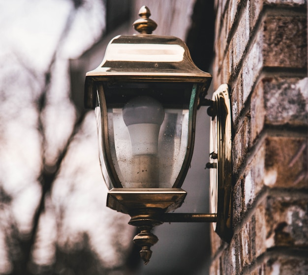 Colpo poco profondo del primo piano di una lanterna della via su una parete di pietra