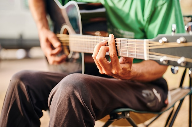 Shallow depth of field guitar chord detail of an unrecognizable boy sitting in a camping chair on a sunny day