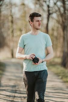Fuoco poco profondo di un fotografo maschio adulto che tiene una macchina fotografica e che cammina attraverso un parco