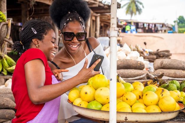 Fuoco poco profondo di un venditore femminile africano che mostra il contenuto in un telefono a un cliente in un mercato