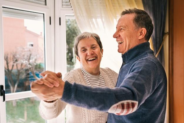 Fuoco poco profondo di una coppia adulta allegra che ride e balla in una casa