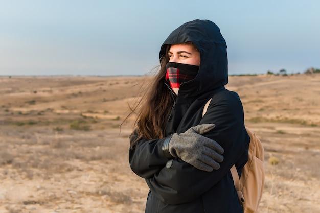 추운 날씨 때문에 자신을 포옹하는 여성의 얕은 초점 근접 촬영
