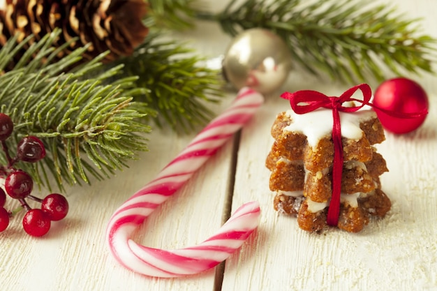 キャンディケインとクリスマスツリーの枝の横にある生姜クッキーの浅い焦点のクローズアップショット