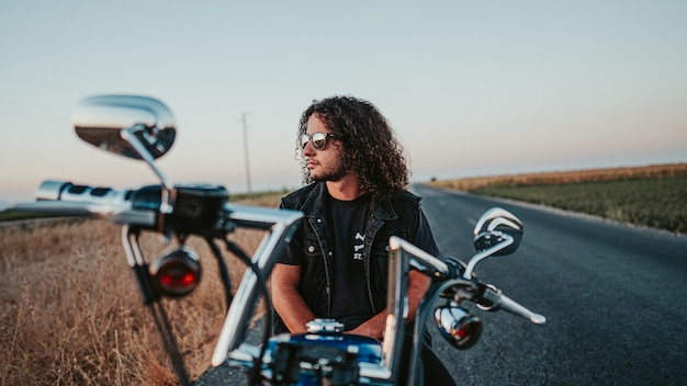 Messa a fuoco superficiale di un bel maschio dai capelli ricci con una giacca di jeans nera sulla sua motocicletta sulla strada
