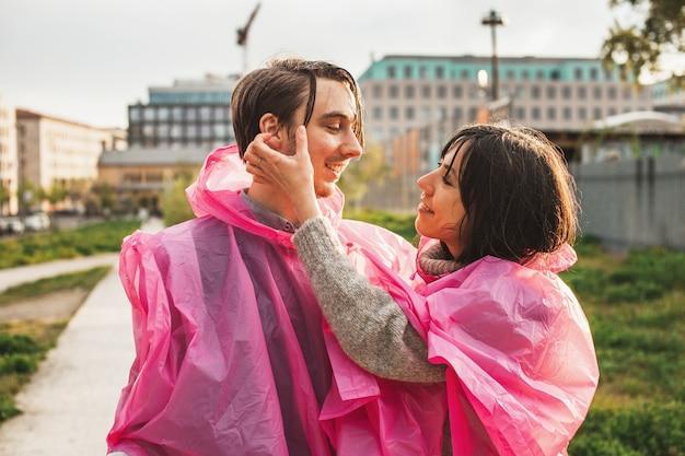 ロマンチックにお互いを見ているピンクのプラスチック製のレインコートを着たカップルの浅い焦点