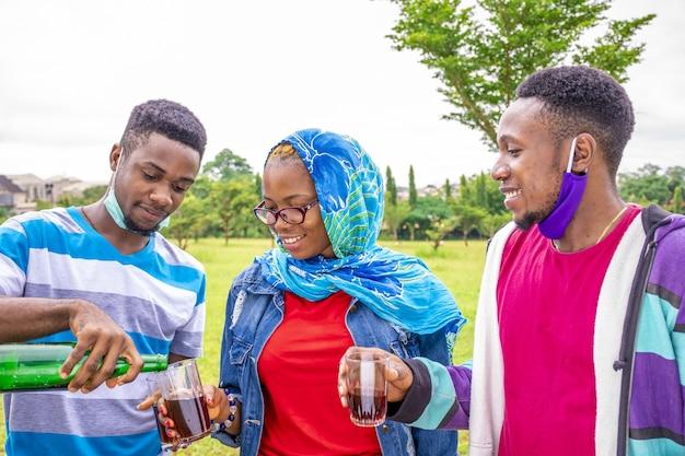 公園でお互いにワインを注ぐフェイスマスクを持つ友人のグループの浅い焦点