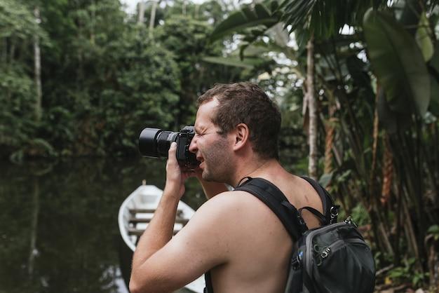 ハイキング中に屋外の写真を撮る上半身裸の写真家の浅い焦点