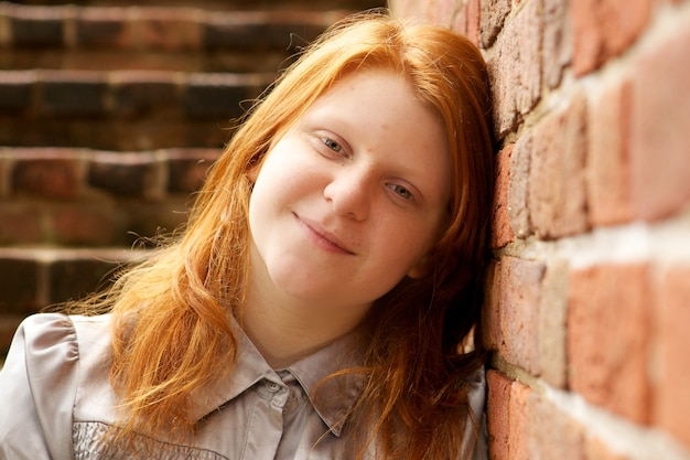 レンガの壁にもたれて若い赤毛の女性の浅いフォーカス