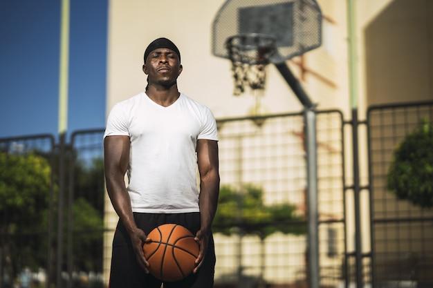 バスケットボールコートに立っている白いシャツを着たアフリカ系アメリカ人男性の浅い焦点
