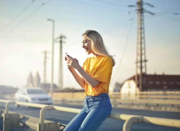 다리 울타리에 기대어 전화로 문자 메시지를 보내는 흥분한 여성의 얕은 초점