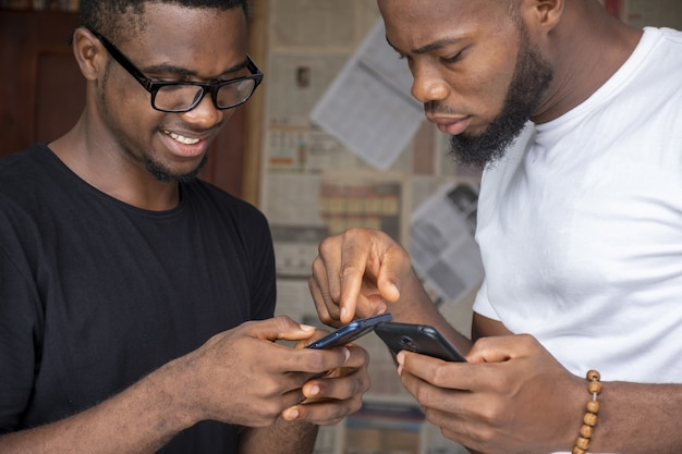 携帯電話でコンテンツを共有する2人の若いアフリカ人男性の浅い焦点