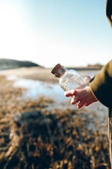 Foto poco profonda del fuoco della persona che tiene la bottiglia di vetro trasparente