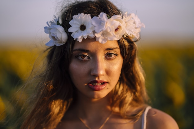 Shallow focus portrait of young caucasian brunette female with flower crown
