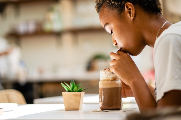 A shallow focus shot of an african american female drinking milkshake