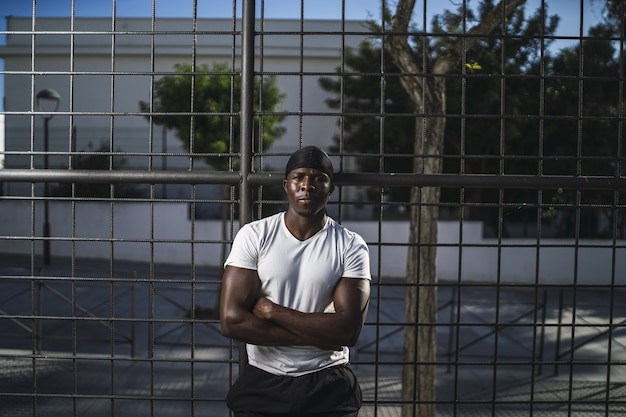 Shallow focus shot of an african-american male in a white shirt leaning on a fence with arms crossed