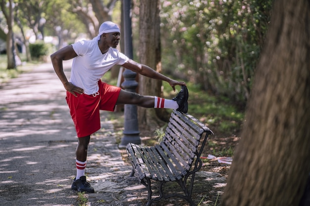Shallow focus shot of an african-american male in a white shirt stretching on a bench at the park