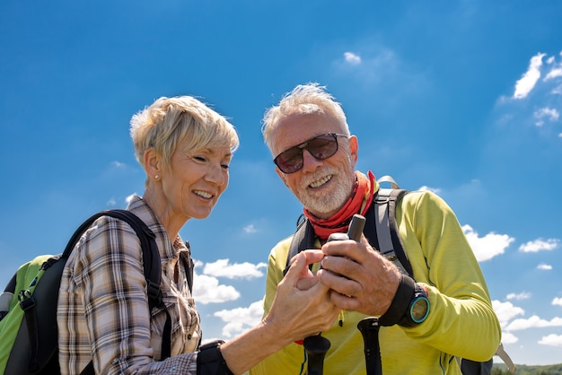 Shallow focus shot of an aged couple using an electrical compass in a big field