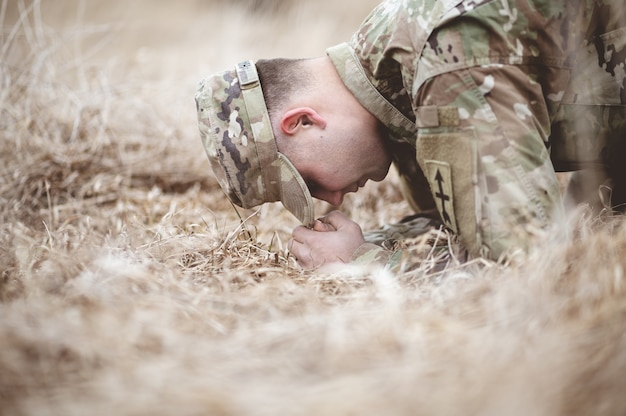 Shallow focus shot of an american soldier kneeling and praying on a dry grass field