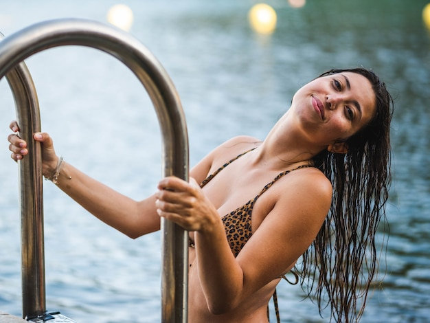 Inquadratura poco profonda di un'attraente donna caucasica che esce dalla piscina