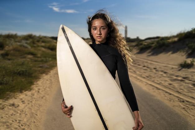Colpo poco profondo del fuoco di una donna attraente che tiene una tavola da surf in mezzo alla strada in spagna