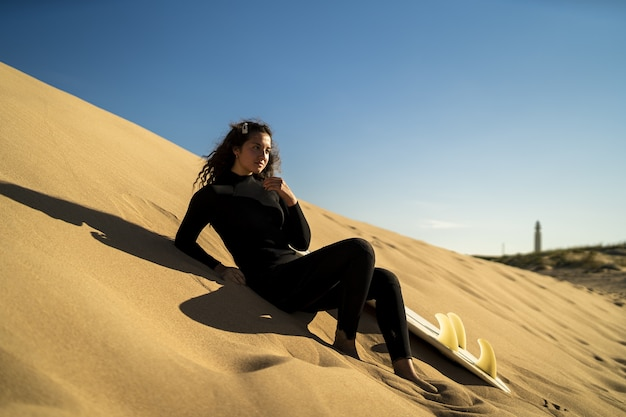 Shallow focus shot of an attractive female posing on a sandy hill with a surfboard on the side