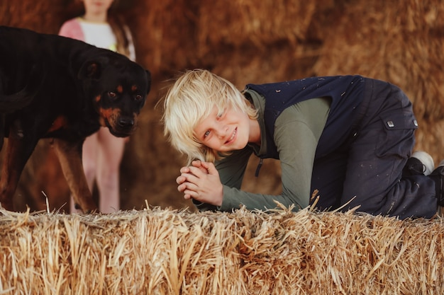Shallow focus shot of a blond australian caucasian boy on the hay bale with a dog
