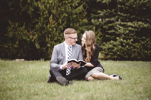 Colpo poco profondo del fuoco di una coppia che parla e gode della reciproca compagnia mentre è seduto in un giardino