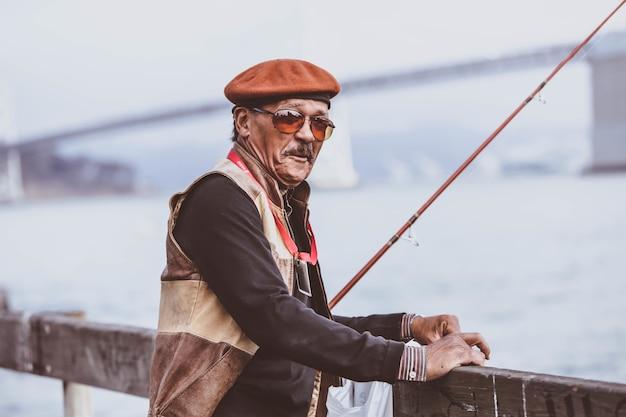 Inquadratura poco profonda di un maschio anziano con una canna da pesca