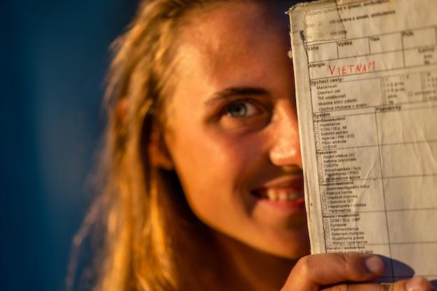 Colpo poco profondo del fuoco della femmina che nasconde la metà del suo fronte dietro una carta