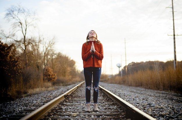 Shallow focus shot of a female standing on train tracks while praying