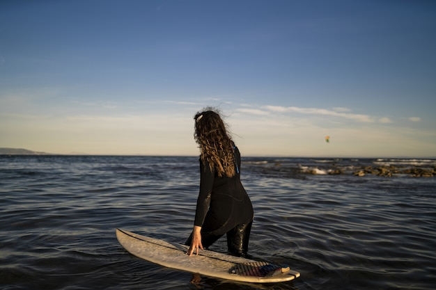 Shallow focus shot of a female walking in the sea with a surfboard on her side