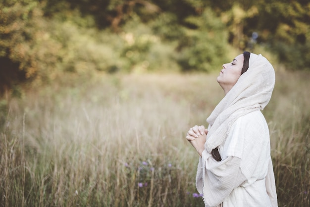 Shallow focus shot of female wearing a biblical robe praying with her head  up towards the sky
