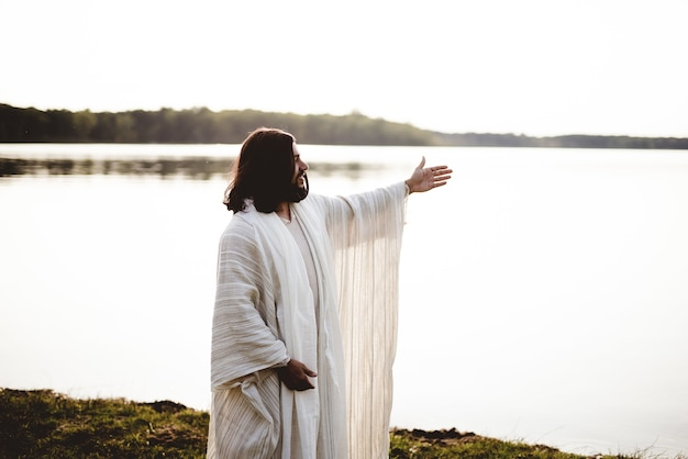 Shallow focus shot of jesus christ with his hands up and looking in the distance