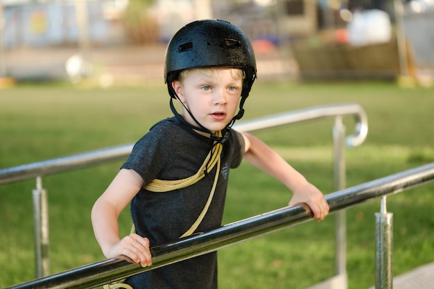 Shallow focus shot of a little boy with a black helmet looking in one direction