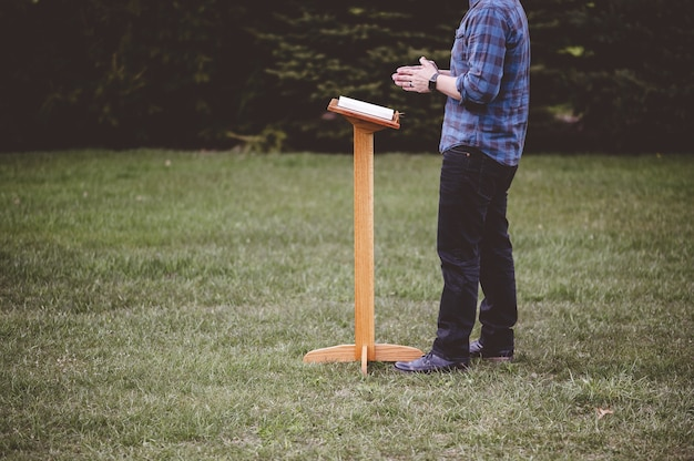 Colpo poco profondo del fuoco di un maschio vicino a uno stand di discorso con un libro aperto