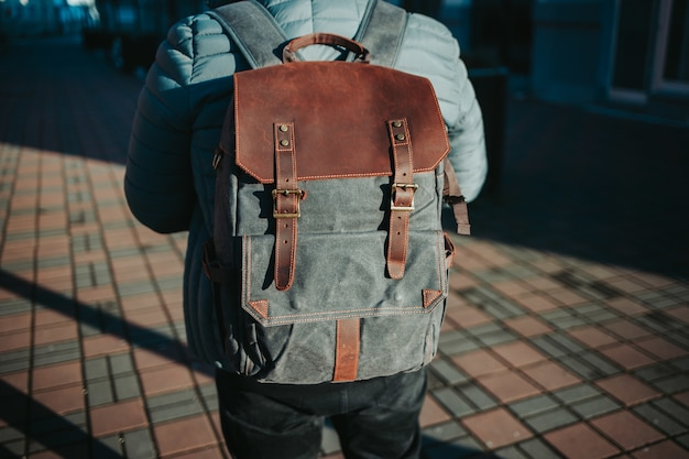 Shallow focus shot of a male wearing a grey and brown rucksack