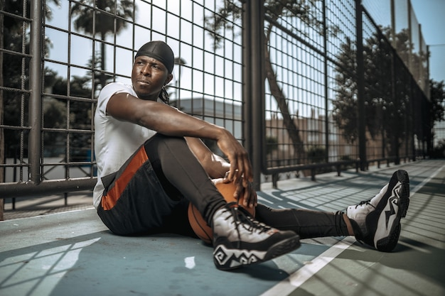 야외 안뜰에서 검은 농구 선수의 얕은 초점 샷