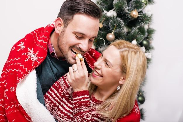 クリスマスツリーの横にある陽気なカップルの浅いフォーカスショット