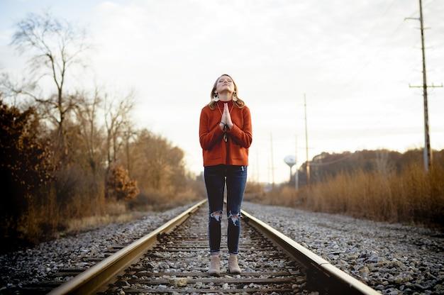 祈りながら電車の線路に立っている女性の浅いフォーカスショット